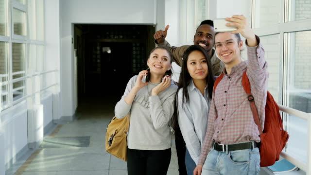 Gruppe-von-multi-ethnischen-Studenten-nehmen-Selfie-auf-Smartphone-Kamera-stehend-im-Flur-der-Universität-Hipster-Mann-hält-Telefon-und-Freunde-stellen-positiv