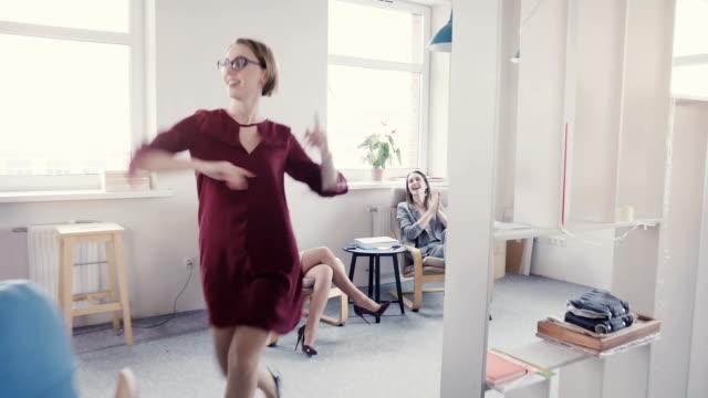 Feliz-líder-femenino-europeo-haciendo-baile-de-Victoria-y-éxito-da-bromea-a-colegas-y-multiétnicas-se-ríe-4-K