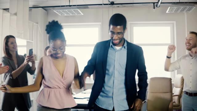 Americanos-africano-trabajadores-masculinos-y-femeninos-haciendo-graciosos-pasos-de-baile-étnico-en-fiesta-de-oficina-con-colegas-multiétnicos-4K