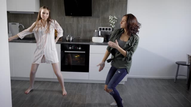 two-young-forefathers-dance-to-energetic-music-in-the-kitchen-funny-women-are-actively-fooling-around