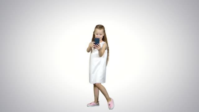 Niña-feliz-tomar-un-selfie-con-un-teléfono-inteligente-sobre-fondo-blanco