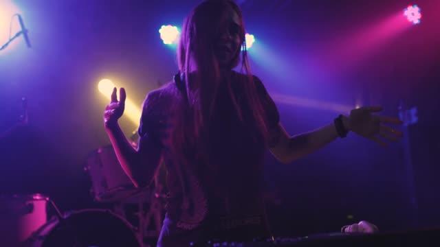 hermosa-joven-DJ-juega-la-música-en-la-mesa-de-mezclas-en-la-discoteca