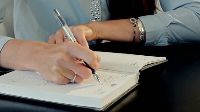 Female-hand-writing-in-notebook