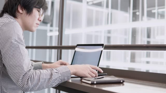 Young-Asian-business-man-using-laptop-computer-and-smartphone-on-wooden-desk-in-working-space-Male-hand-typing-on-laptop-keyboard-Freelance-lifestyle-in-digital-age-concept-