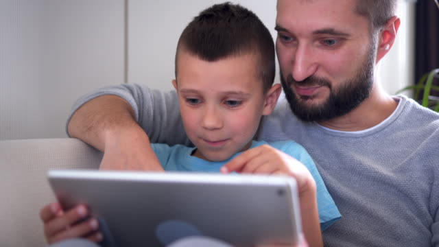 Delighted-father-hugging-son-while-using-tablet-on-sofa
