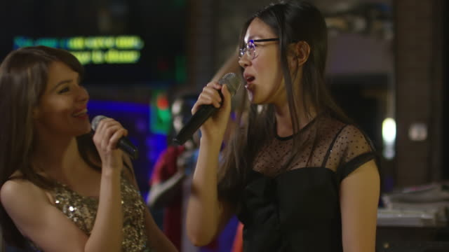 Joyful-Women-Singing-in-Karaoke-Bar