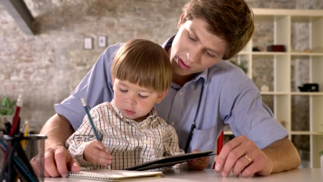 Little-boy-sitting-with-his-young-father-at-table-and-writing-on-paper-looking-at-tablet-modern-office-background