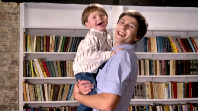 Young-father-holding-his-little-son-and-jumping-in-library-smiling-and-happy