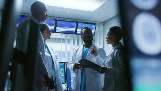 Low-Angle-Shot-of-the-Meeting-of-the-Team-of-Medical-Scientists-in-the-Brain-Research-Laboratory-Neurologists-/-Neuroscientists-Having-Analytical-Discussion-Surrounded-by-Monitors-Showing-CT-MRI-Scans-
