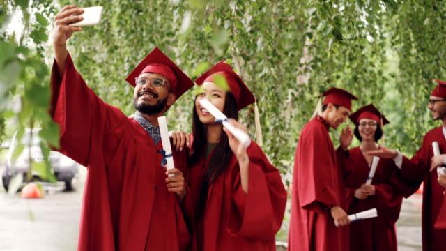 Dos-estudiantes-de-raza-mixta-están-tomando-selfie-con-diplomas-de-graduación-con-Birretes-y-togas-guy-tiene-smartphone-y-tomar-foto-