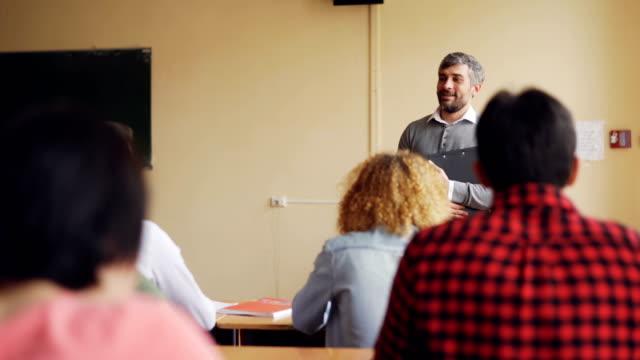 Amable-maestro-está-hablando-con-sus-alumnos-comprobar-conocimientos-joven-es-levantar-la-mano-y-pregunta-otros-estudiantes-están-escuchando-Enseñanza-y-el-aprendizaje-de-concepto-