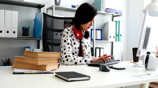 mujer-con-auriculares-rojo-con-hombros-hojeando-el-libro-y-el-uso-del-ordenador-portátil