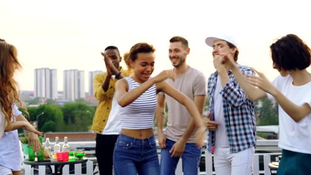 Chica-bonita-mestiza-es-bailando-con-amigos-y-riendo-con-fiesta-en-la-azotea-Entretenimiento-fiesta-al-aire-libre-y-el-concepto-de-estilo-de-vida-moderno-