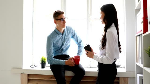 Kollegen-reden-und-Kaffeetrinken-bei-Fenster-im-Büro