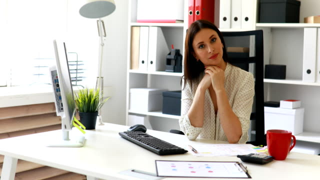 businesswoman-sitting-at-desk-in-front-of-window-and-looking-in-camera