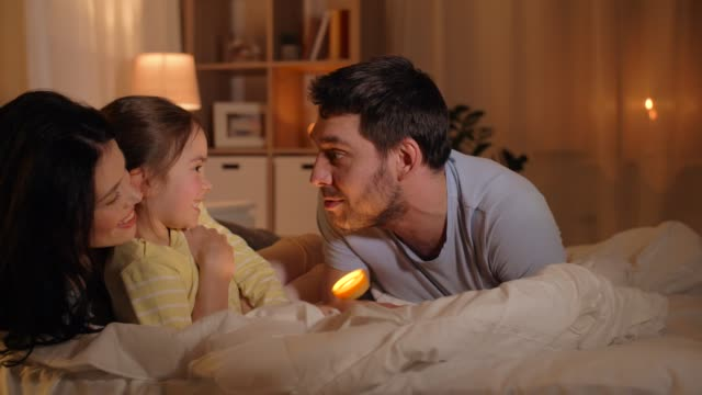 happy-family-with-torch-light-in-bed-at-home