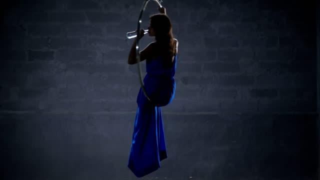 Beautiful-girl-in-long-dress-drinks-water-in-the-aerial-hoop