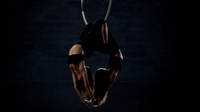 Two-beautiful-gymnasts-performs-trick-at-the-aerial-hoop