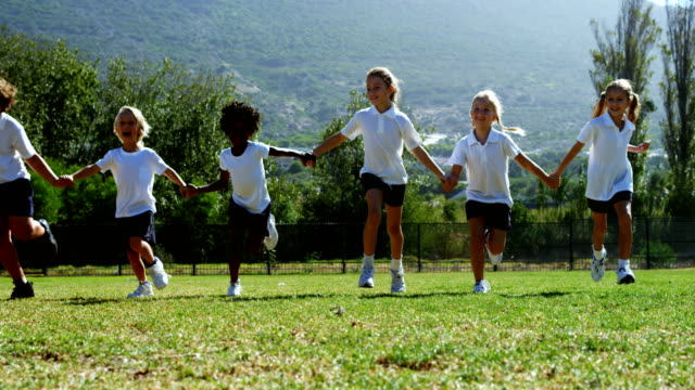 School-kids-holding-hands-and-running-in-park