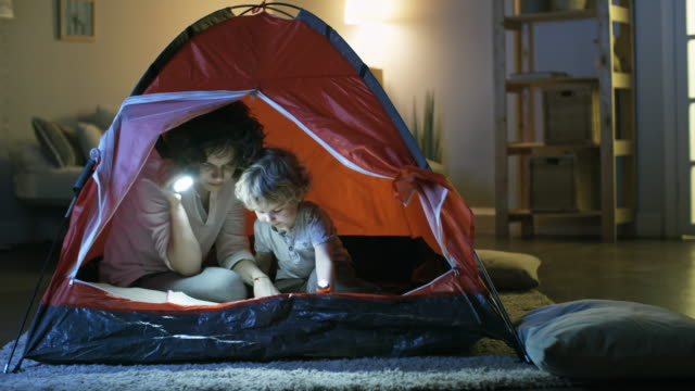 Mother-and-Son-Reading-Book-in-Tent