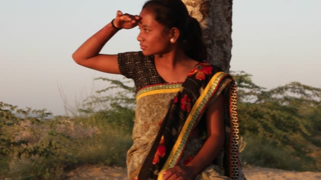 Indian-teenager-beautiful-girl-waiting-watching-at-a-hill-top-under-a-tree-on-a-summer-day-in-eager-love-happy-joy-sun-tropical-hot-bright-sunshine-content-looking-at-camera-handheld-stabilized