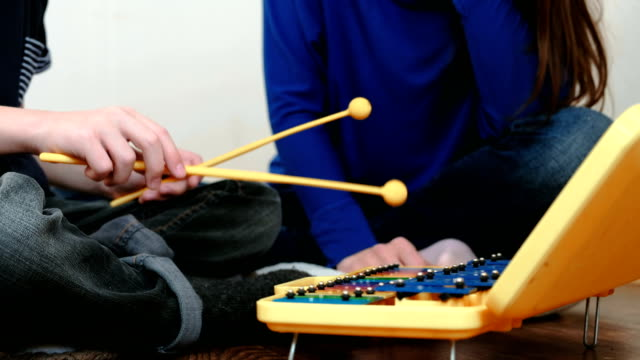 Playing-music-instrument-Closeup-boy-s-hand-playing-on-xylophone-and-his-mom-sitting-near-him-