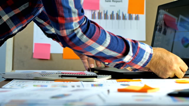 Hand-of-businessmen-using-laptop-examine-account-calculated-financial-reporting-with-charts-graphs-The-concept-of-business-finance-and-accounting-and-Business-startup-Online-Marketing