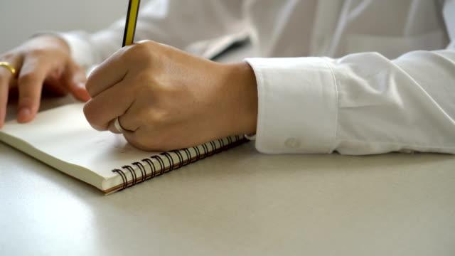 Escribir-lista-de-notas-en-el-cuaderno-con-el-lápiz-de-la-mano-de-empresario-