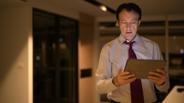 Destacó-maduro-hombre-de-negocios-en-la-oficina-por-la-noche-con-tableta-Digital
