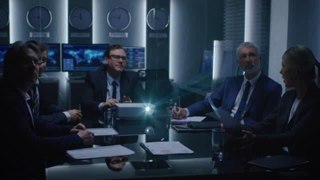 Funcionarios-del-gobierno-ejecutivos-de-negocios-viendo-la-presentación-en-la-sala-de-conferencias-Proyector-de-trabajo-sobre-la-mesa-Gente-de-negocios-tener-discusión-negociación-y-resolución-de-problemas-