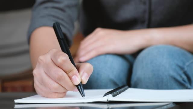 Mano-de-una-mujer-escribiendo-en-un-cuaderno-en-blanco-blanco-sobre-mesa