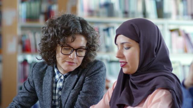 Frau-in-Hijab-arbeiten-mit-Lehrerin-bei-Lektion
