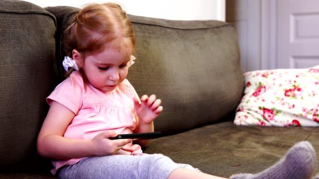 Niña-jugando-con-un-smartphone-y-mirando-a-la-cámara