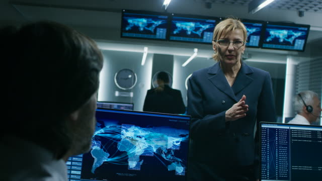 Female-Chief-Operative-Officer-talks-to-Cyber-Security-Dispatchers-Working-on-Personal-Computer-Showing-Traffic-Data-Flow-in-the-System-Control-Room-