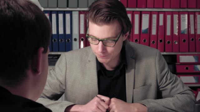 Businessmen-sitting-at-desk-and-talking