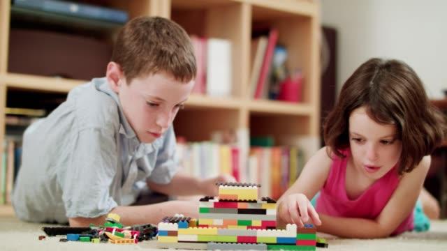 Dos-niños-jugando-con-ladrillos-de-lego-en-casa