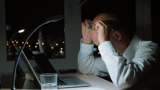 Tired-businessman-working-by-notebook-and-doing-neck-massage-in-night-office