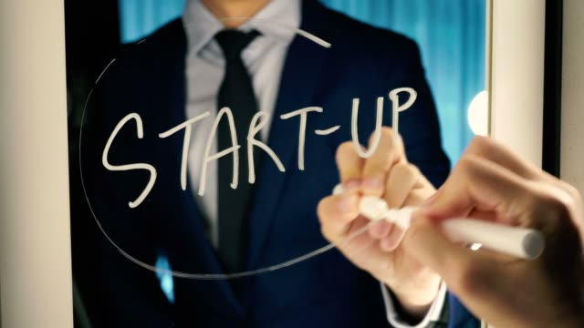 Smart-business-man-writing-the-word-Start-up-on-the-mirror-board---Start-up-tech-business-text-letter