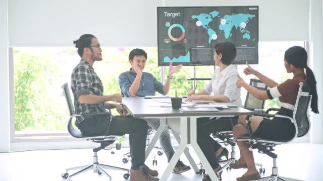 Reunión-de-negocios-Pequeño-en-marcha-reunión-de-negocios-en-la-habitación-El-equipo-asiático-con-hombre-y-mujer-acabar-su-trabajo-y-celebrar-sentarse-hacia-cámara-Nuevo-modelo-de-negocio-en-marcha-conceptos-