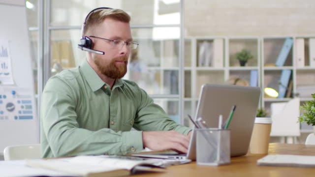 Call-Center-Manager-Working-on-Laptop-and-Video-Calling