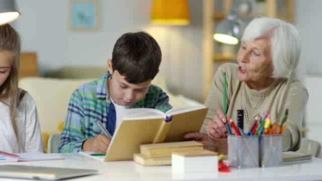 Children-Doing-Homework-with-Help-of-Grandma
