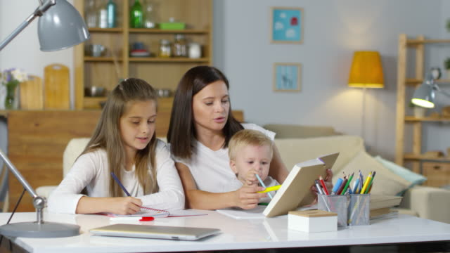 Beautiful-Mom-Helping-Daughter-with-Homework-and-Taking-Care-on-Baby-Son