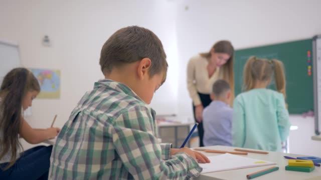 Porträt-von-lächelnden-Schuljunge-am-Schalter-während-der-Lektion-im-Klassenzimmer-in-der-Grundschule-auf-unscharfen-Hintergrund