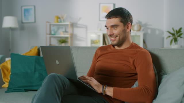 Handsome-Man-Uses-Laptop-Computer-while-Sitting-on-Sofa-at-Home-Man-Working-Browsing-Through-Internet-from-His-Cozy-Living-Room-
