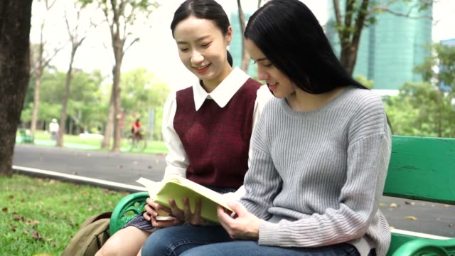 Two-young-female-friends-reading-a-book-together-in-public-park-outdoors-Multi-ethnic-diversity-