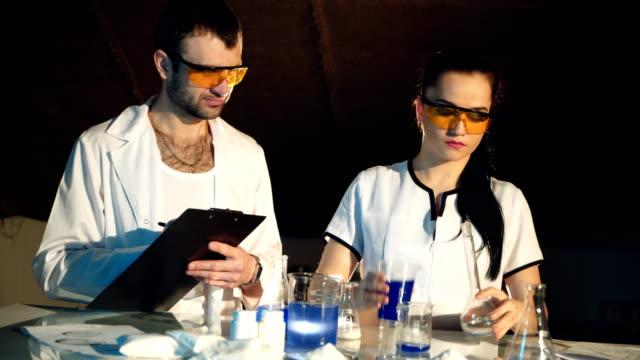 Laborant-es-examinar-la-reacción-de-una-sustancia-en-un-tubo-de-ensayo-mientras-revuelve-