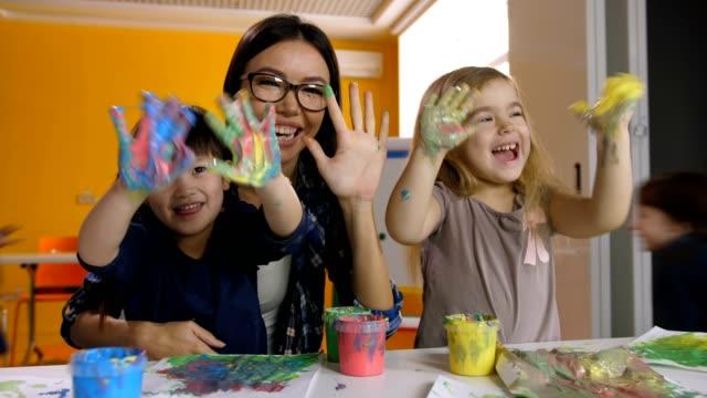 Niños-y-maestro-con-las-manos-en-la-pintura-en-lección-de-arte