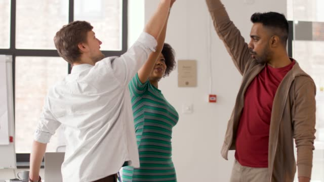happy-creative-team-making-high-five-at-office