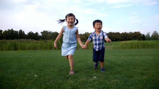 Niños-asiáticos-alegres-corriendo-juntos-en-el-Parque