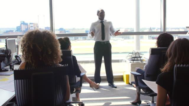 Afroamerikanische-manager-spricht-zu-Kollegen-im-Büro